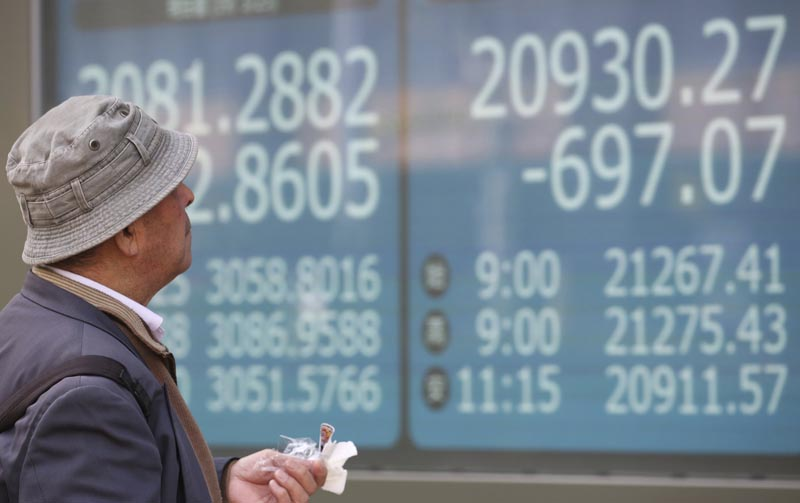 man looks at an electronic stock board of a securities firm in Tokyo, Monday, March 25, 2019. Shares were sharply lower in Asia on Monday after Wall Street ended last week with a broad retreat. Photo: AP