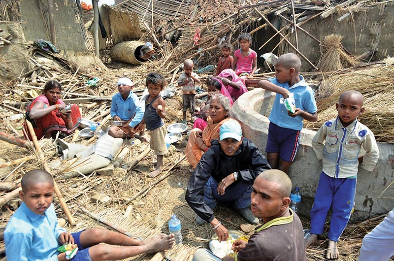 Natural disaster survivors eating amidst the destroyed structures  in Bhaluhi, Birgunj, on Monday, April 1, 2019. Photo: THT
