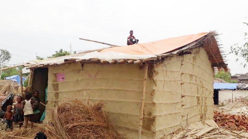 A storm victim covering the roof of his hut with tarpaulin after it began to leak, in Pheta Rural Municipality, Bara, on Sunday, April 21, 2019. Photo: THT