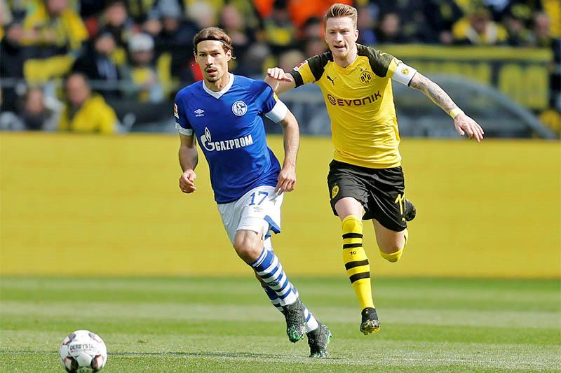 Schalke's Benjamin Stambouli in action with Borussia Dortmund's Marco Reus. Photo: Reuters