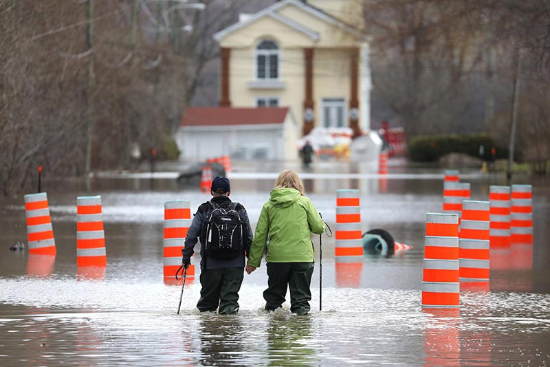 A man and woman hold hands while walking through a flooded residential area in Gatineau, Quebec, Canada, on Wednesday, April 24, 2019. Photo: Reuters