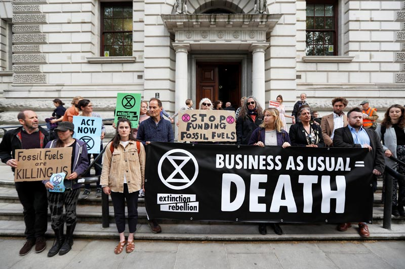 Climate protesters hold placards in front of HM Treasury in Westminster during the Extinction Rebellion protest in London, Britain April 25, 2019. Photo: Reuters
