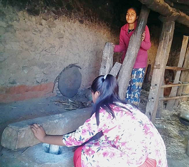 Women grinding food grains in traditional tool known as Dhikki, in Bhojpur district, on Sunday, April 07, 2019. Photo: Niroj Koirala