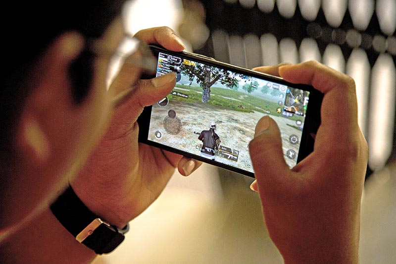 An Indian boy plays an online game PUBG on his mobile phone sitting outside his house  in Hyderabad, India, Friday, April 5, 2019. A boyu2019s suicide in India after his mother scolded him for playing the popular online game PlayerUnknownu2019s Battlegrounds has inflamed a debate across the country over whether the game should be banned. Photo: AP