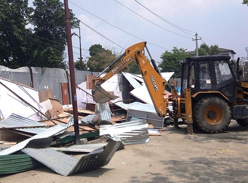 An excavator demolishing illegal structures at Khula Manch in Kathmandu, on Saturday. Photos: RSS