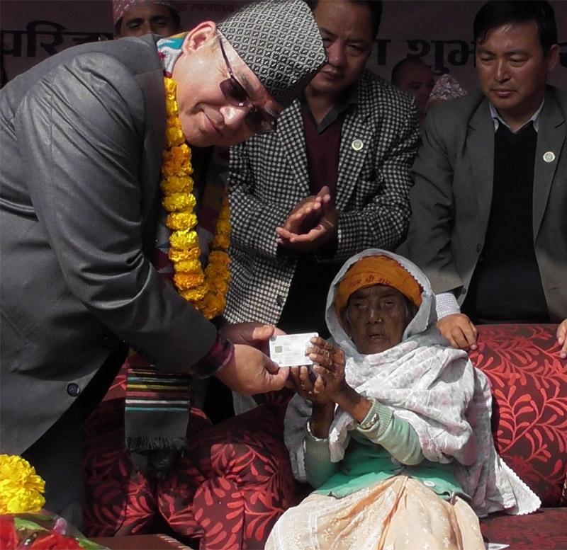 Senior citizen Bhagwati Devi Bhandari receiving the first ever National Identity Card from Minister for Home Affairs Ram Bahadur Thapa, in Panchthar district, on November 19, 2018. Photo: Laxmi Gautam/THT