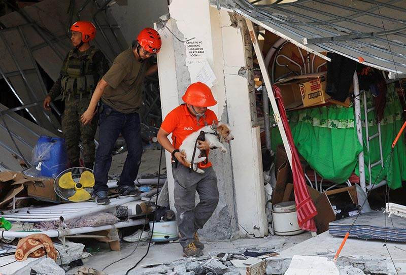 A rescuer carries a search dog as they try to reach survivors at a collapsed four-storey building following an earthquake in Porac town, Pampanga province, Philippines, April 23, 2019. Photo: Reuters