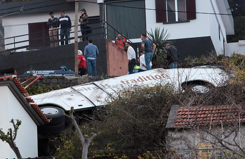 People stand next to the wreckage of a bus after an accident in Canico, in the Portuguese Island of Madeira, April 17, 2019. Photo: Reuters