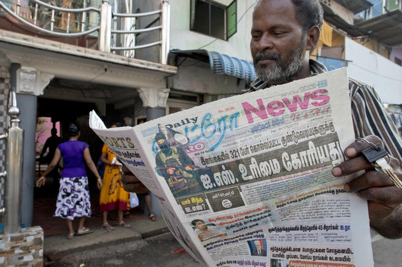 A man reads a newspaper with a lead story on Islamic State taking responsibility of Easter Sunday terror attacks in Colombo, Sri Lanka, Wednesday, April 24, 2019. Photo: AP