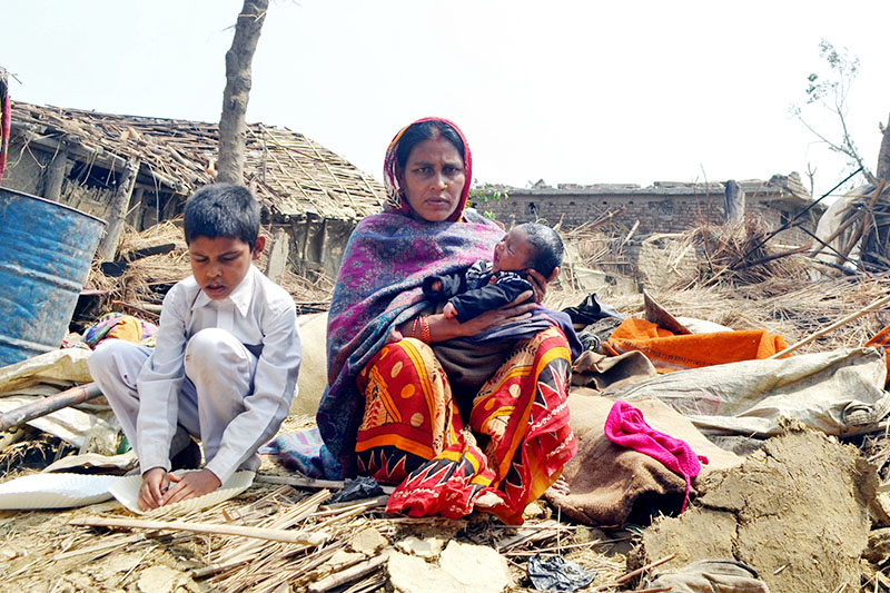 A new mother and her child sit on debris infront of ther house in Varbaliya. Photo: Ram Sarraf/THT