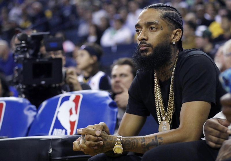FILE - In this March 29, 2018, file photo, rapper Nipsey Hussle watches an NBA basketball game between the Golden State Warriors and the Milwaukee Bucks in Oakland, California. Photo:AP