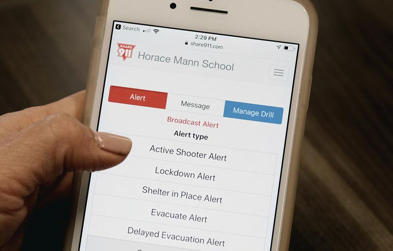 In this Monday May 13, 2019 photo Juliet Fine, principal at Beverly Hills Unified School District's K-8 Horace Mann School shows the Share 911 phone application on her cell phone during an interview in her office in Beverly Hills, Calif. The district is among 200 in the country using the Share911 app. Photo: AP