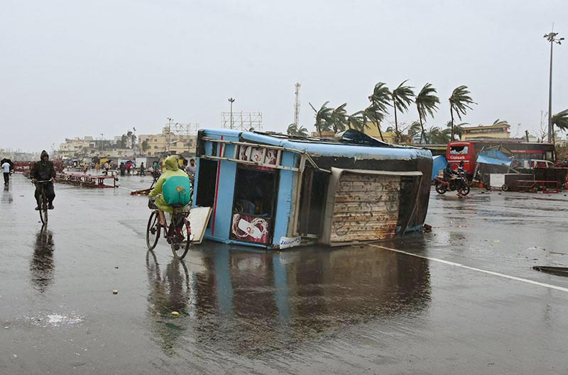 People move past a damaged vehicle after Cyclone Fani hit Puri, in the eastern state of Odisha, India, on Friday, May 3, 2019. Photo: Reuters