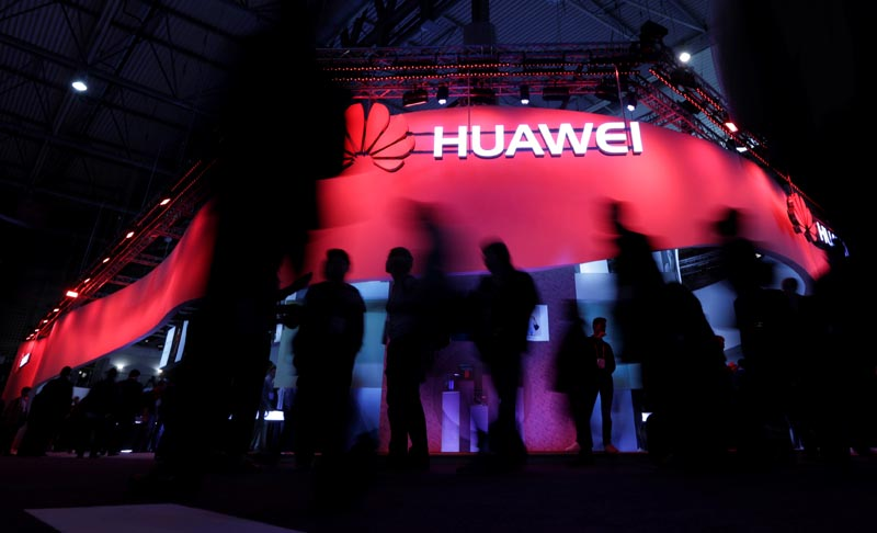 FILE: Visitors walk past Huawei's booth during Mobile World Congress in Barcelona, Spain, February 27, 2017. Photo: Reuters/file