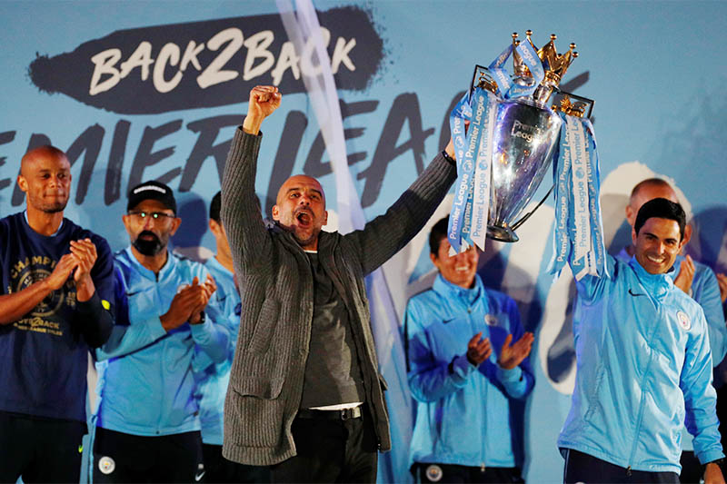 FILE - Manchester City manager Pep Guardiola and assistant coach Mikel Arteta celebrate winning the Premier League with the trophy. Photo: Reuters