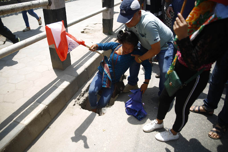 A woman falls on a pothole during a rally to celebrate Labour Day also referred as May Day in Kathmandu, Nepal on Wednesday, May 01, 2019.Photo: Skanda Gautam