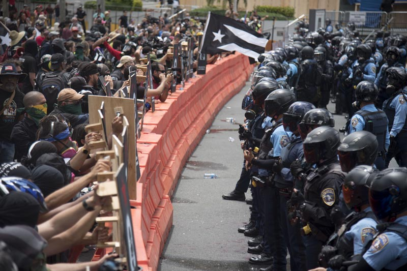Demonstrators holding wooden shields are confronted by police during a protest against the Federal Fiscal Control Board, as part of the May Day celebration in San Juan, Puerto Rico, Wednesday, May 1, 2019. Photo: AP