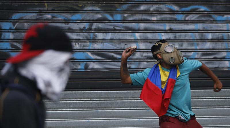 An anti-government protester winds up to throw a rock at security forces during clashes between the two, in Caracas, Venezuela, Wednesday, May 1, 2019. Photo: AP