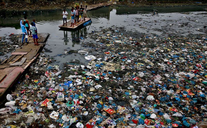 A man guides a raft through a polluted canal littered with plastic bags and other garbage in Mumbai, India Sunday, October 2, 2016. Photo: AP/File