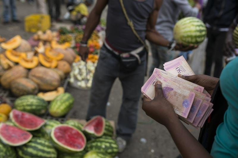 A fruit vendor counts his Bolivares in the Coche Market in Caracas, Venezuela, Thursday, May 2, 2019. Photo: AP