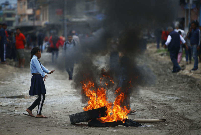 A school girl walks past burning tyres during a protest against the delay in blacktopping of roads, at Thali, in Kathmandu, on Tuesday, June 11, 2019. Photo: Skanda Gautam/THT
