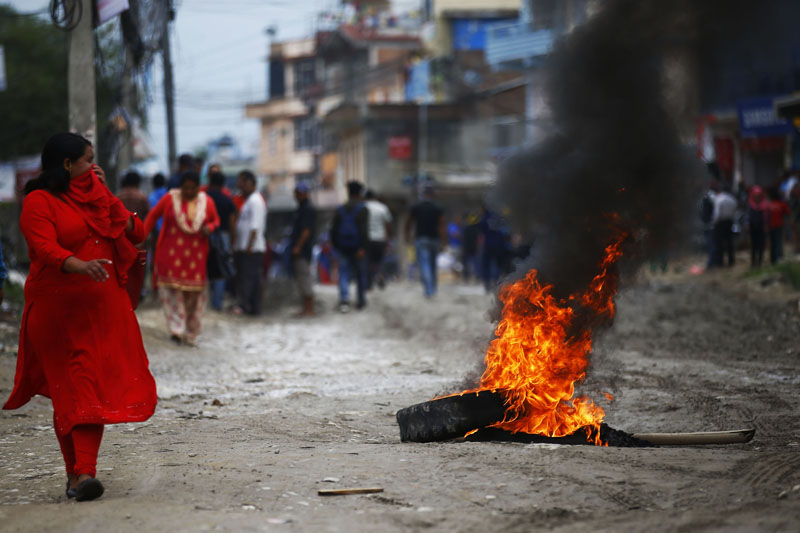 A woman walks past burning tyres during a protest against the delay in blacktopping of roads, at Thali, in Kathmandu, on Tuesday, June 11, 2019. Photo: Skanda Gautam/THT
