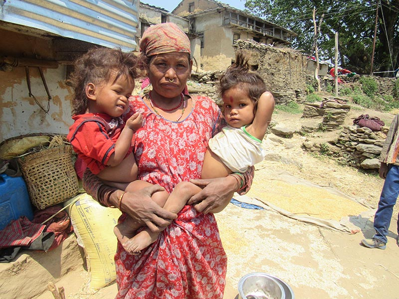 A mother stands with her two children in Amkot of Budhiganga Municipality-1 in Bajura district, on June 19, 2019. Photo: Prakash Singh/THT
