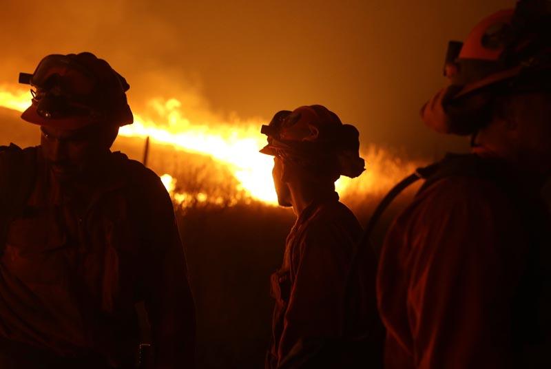 California Department of Corrections and Rehabilitation inmates stand guard as flames from the Butte Fire approach a containment line near San Andreas, California, September 12, 2015. Photo: AP/File