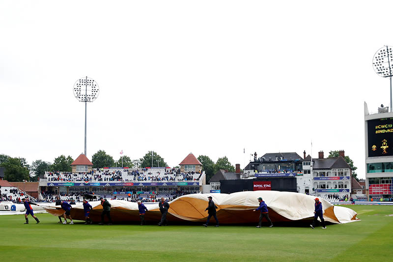 General view as groundstaff pull the covers off the pitch after a rain delay. Photo: Reuters