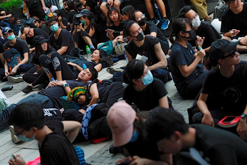 Demonstrators rest outside the Legislative Council building during a demonstration demanding Hong Kong's leaders to step down and withdraw the extradition bill, in Hong Kong, China June 21, 2019. Photo: Reuters