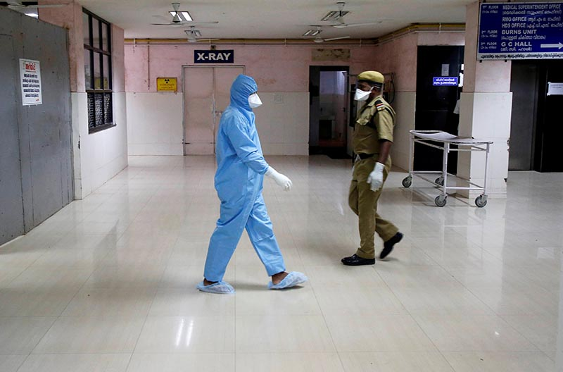 A medical staff wearing protective clothing and a security guard walk after preparing isolated wards at a hospital in Kochi, India June 3, 2019. Photo: Reuters