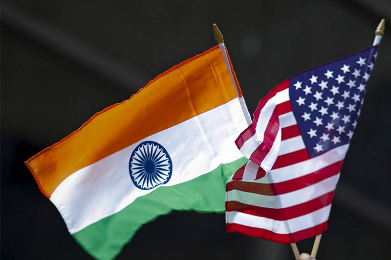 FILE PHOTO: A man holds flags of India and the US while people take part in the 35th India Day Parade in New York, US August 16, 2015. Photo: Reuters