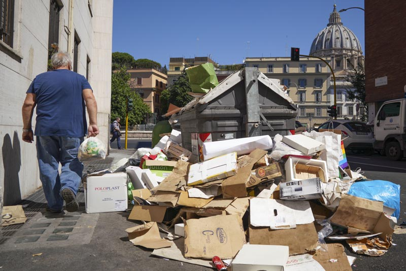 In this photo taken on Monday, June 24, 2019, a man walks past a pile of garbage as St Peter's Dome is visible in background, in Rome. Photo: AP
