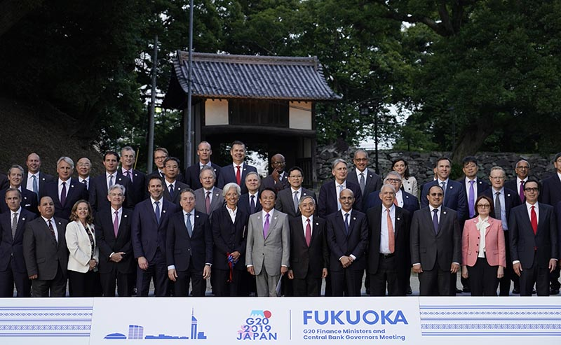 Japan's Finance Minister Taro Aso, centre, poses next to IMF Managing Director Christine Lagarde, centre left, and Bank of Japan Governor Haruhiko Kuroda, centre right, during a family photo of the G20 finance ministers and central bank governors meeting Saturday, June 8, 2019. The G20 finance ministers and central bank governors meeting is taking place in Fukuoka June 8-9. Photo: Franck Robichon/Pool Photo via AP