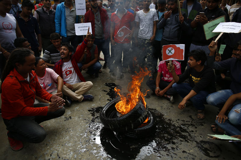 Student Union's agitating cadres shout slogans next to burning tyres during a protest against the delay in blacktopping of roads, at Thali, in Kathmandu, on Tuesday, June 11, 2019. Photo: Skanda Gautam/THT