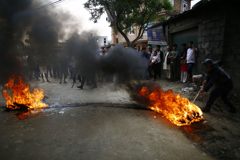 Police attempt to remove burning tyres from the road during a protest against the delay in blacktopping of roads, at Thali, in Kathmandu, on Tuesday, June 11, 2019. Photo: Skanda Gautam/THT