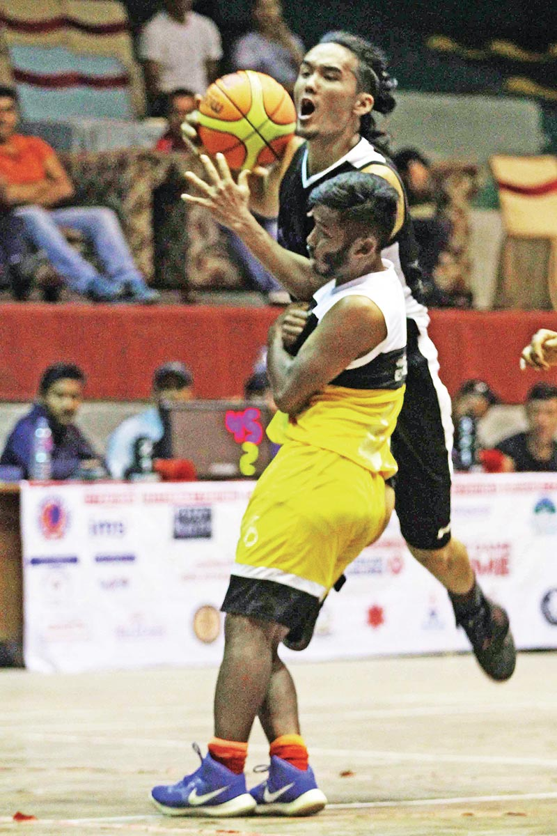Bijay Burja (right) of Times drives the ball against Sandesh Tamang of NPC during their Kwiks Nepal Basketball League match in Kathmandu on Wednesday. Photo: Udipt Singh Chhetry / THT
