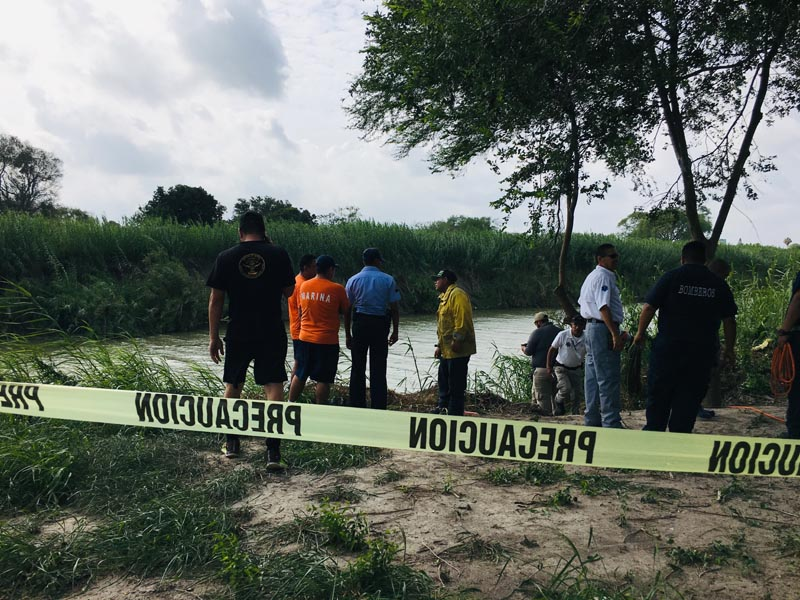 Authorities stand behind yellow warning tape along the Rio Grande bank where the bodies of Salvadoran migrant Oscar Alberto Martu00ednez Ramu00edrez and his nearly 2-year-old daughter Valeria were found, in Matamoros, Mexico, Monday, June 24, 2019, after they drowned trying to cross the river to Brownsville, Texas. Photo: AP