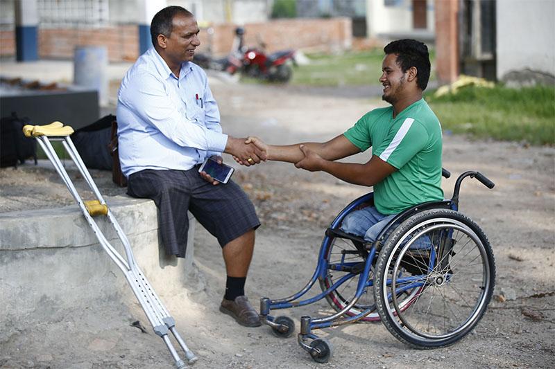 Ramesh Khatri, 21, a student with disability shakes hand with his principal after scoring B-grade in the SEE examinations at Shree Khagendra New Life Special Education School, in Jorpati, Kathmandu, on Thursday, June 27, 2019. Photo: Skanda Gautam/THT