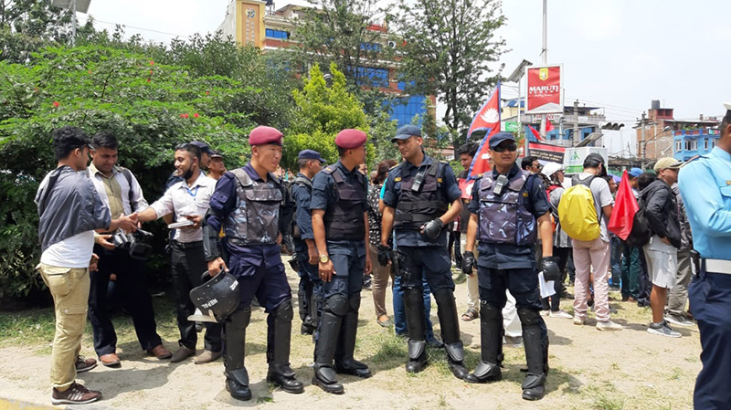 Security personnel converse as crowd starts gathering to protest against the Guthi Bill, at Maitighar, in Kathmandu, on Wednesday, June 19, 2019. Photo: THT Online