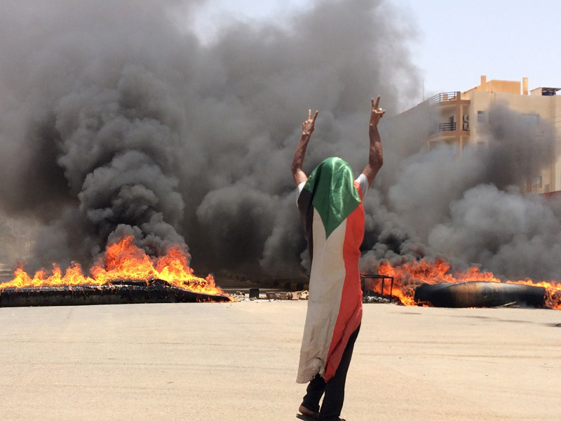 A protester wearing a Sudanese flag flashes the victory sign in front of burning tires and debris on road 60, near Khartoum's army headquarters, in Khartoum, Sudan, Monday, June 3, 2019. Photo: AP