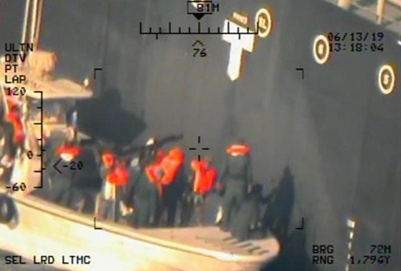 This image released by the US Department of Defense on Monday, June 17, 2019, and taken from a US Navy helicopter, shows what the Navy says are members of the Islamic Revolutionary Guard Corps Navy removing an unexploded limpet mine from the M/T Kokuka Courageous. Photo: US Department of Defense via AP