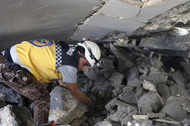 This photo posted and provided by the Syrian Civil Defense White Helmets, which has been authenticated based on its contents and other AP reporting, shows a Civil Defense worker searching for victims under the rubble after an airstrike by Syrian government forces hit the town of Maaret al-Numan in Idlib province, Syria, Saturday, June. Photo: Syrian Civil Defense White Helmets via AP