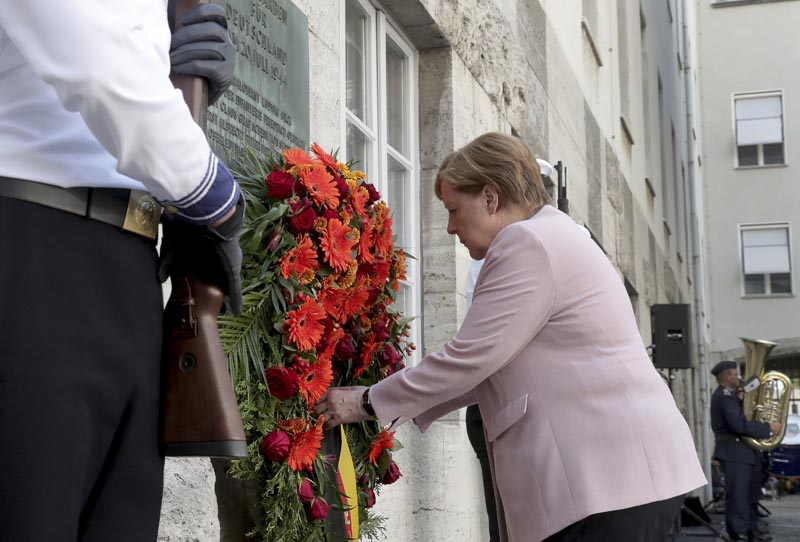 German Chancellor Angela Merkel adjusts a wreath during a memorial event at the Defence Ministry in Berlin, Germany, Saturday, July 20, 2019. Photo: AP