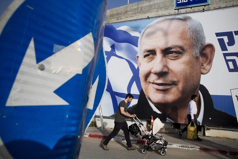 FILE - In this April 7, 2019 file photo, a man walks by an election campaign billboard showing Israel's Prime Minister Benjamin Netanyahu, the Likud party leader, in Tel Aviv, Israel. Photo: AP