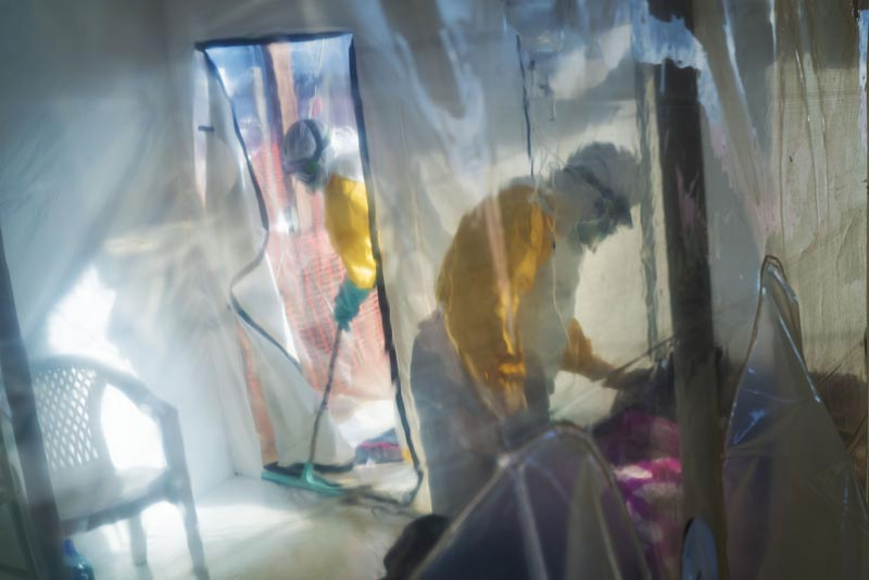 In this photograph taken Saturday 13 July 2019, health workers wearing protective suits tend to to an Ebola victim kept in an isolation cube in Beni, Congo DRC. Photo: AP