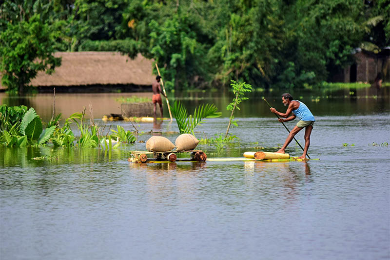 A man uses a makeshift raft to move his paddy to a safer place in a flooded area in Morigaon district in the northeastern state of Assam, India, on Tuesday, July 16, 2019. Photo: Reuters