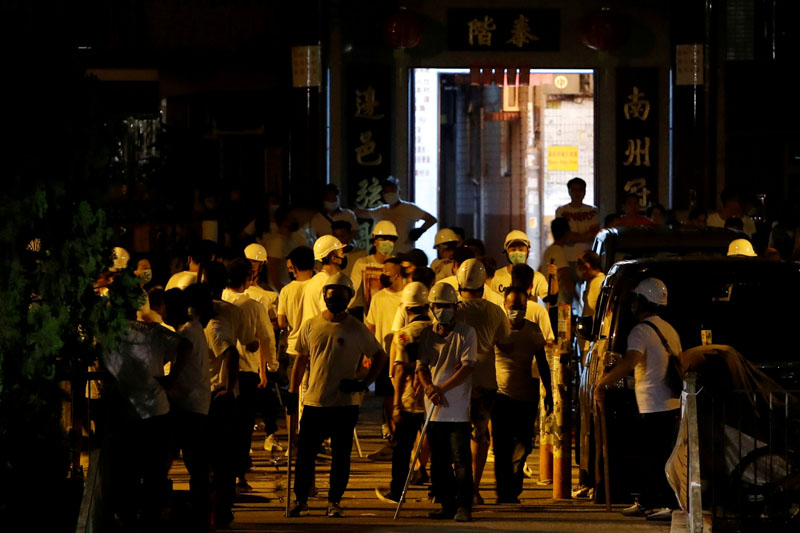 Men in white T-shirts and carrying poles are seen in Yuen Long after attacking anti-extradition bill demonstrators at a train station in Hong Kong, China, July 22, 2019. Photo: Reuters