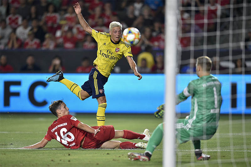 Bayern Munich goalkeeper Manuel Neuer (1) blocks a shot by Arsenal midfielder Mesut Ozil (10) while defender Kehl (46) defends during the first half of the International Champions Cup soccer series at Dignity Health Sports Park. Mandatory Credit: Kelvin Kuo-USA TODAY Sports