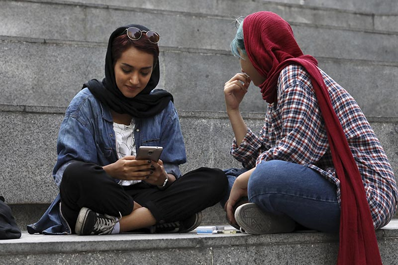 FILE: An Iranian woman works on her cell phone while spending an afternoon on steps outside of a shopping mall in northern Tehran, Iran on Tuesday, July 2, 2019. Photo: AP